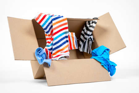 Bright colored clothing in recyclable eco-friendly cardboard box on white background, copy space. Gathering things for charity or fair. Packing for stuff for moving.