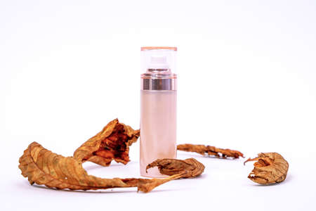 Creative advertising of cosmetic product for autumn skincare containing natural ingredients in beautiful bottle with dispenser on white background, dry tree leaves around for decoration, copy space.