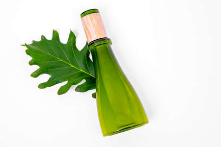 Top view on cosmetic bottle of green glass lying down on oak leaf. White background, copy space. Natural botanical product concept. Stock Photo