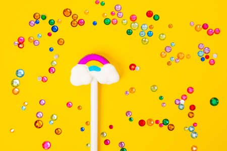 Pencil with eraser or toy in shape of rainbow with clouds on stick lies on yellow background, colorful plastic and glass gems and beads are scattered around, top view. Stock Photo