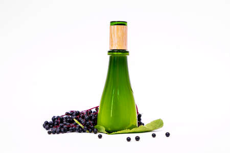 The close up cosmetic bottle of green glass with black bird cherry bunch and leaves. Empty white background, copy space. Stock Photo
