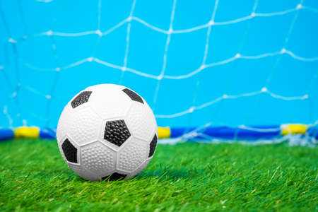 Miniature toy soccer ball lies on green grass of artificial turf of football field against the backdrop of a grid of football goals, blue background, front view, close up. Equipment for outdoor activities and sports