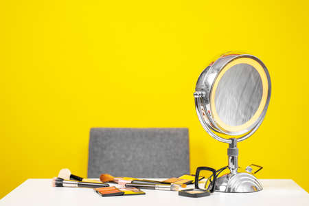 Workplace of makeup artist or beauty blogger on yellow background, copy space. Tools are on table - brushes and palettes for powder, blush, contouring, mirror with illumination and magnifying lens.
