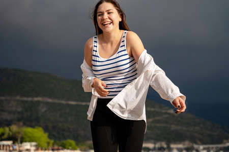 Happy young brunette woman in white shirt and striped top walks around resort town and laughs, posing against mountains and black gloomy sky. The calm before the storm.