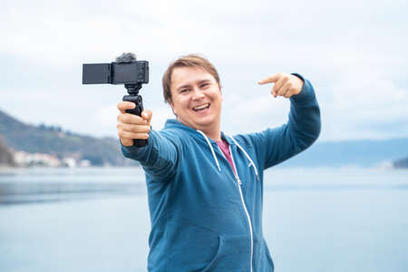 Smiling happy man with professional camera takes photo on background of beautiful landscape with lake and mountains. Entertaining and informative vlog of travel blogger.