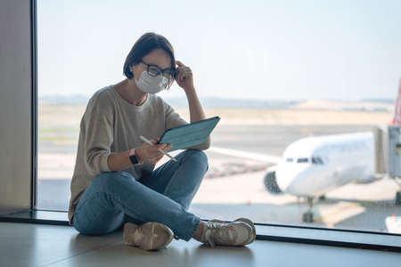 Female freelancer in medical mask sits in lotus position on airport floor waiting for flight to depart, and works using digital tablet and pencil. Outside the window are planes. Life during pandemic.