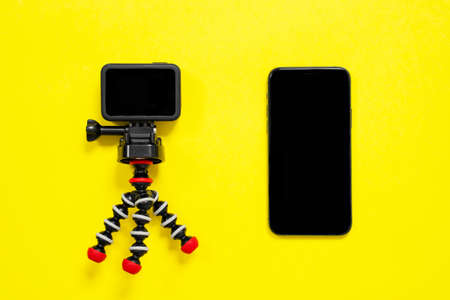 Action camera on compact portable tripod and mobile phone lie on yellow background, top view, copy space for advertising. Modern technologies for bloggers and streaming.