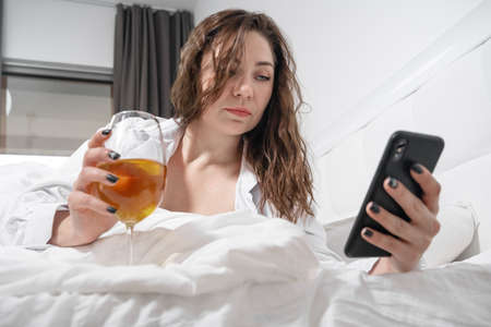 Young woman in white shirt and with glass of wine lies in bed on day off and checks social networks or notifications on mobile phone. Female freelancer works right in bedroom using smartphone.