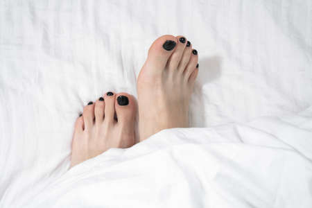 Female bare feet with black pedicure on toes stick out from under warm cozy white blanket, top view, copy space. Lazy weekend or vacation at home in bed.