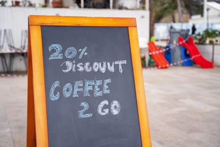 Board with wooden frame with message about discount on takeaway coffee written in colored chalk stands on street next to city cafe. Modern life in hurry and bustle.