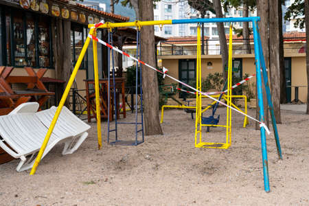 Faulty playground with swings in park is closed for repairs and fenced with red and white signal tape. Prohibition of visiting public places during state quarantine