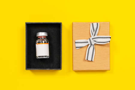 Glass vial with rare medicine or vaccine for new disease in open cardboard box, lid decorated with ribbon bow next to it, top view, yellow background, copy space for advertising.