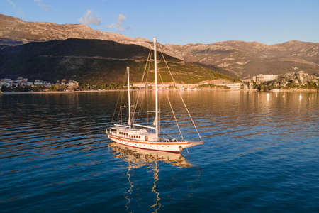 Large vintage sailboat is anchored in the middle of sea bay, illuminated by golden rays of sun. Beautiful seascape with calm water surface and mountains covered with forest.