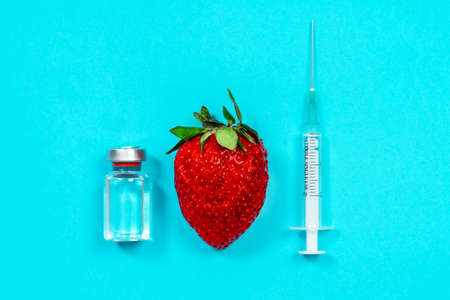 Tools and medicines for treatment, blue background, top view, copy space for advertising. First aid in case of allergic reaction to berries. Insulin syringe and prohibited foods for diabetes