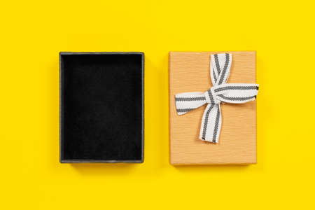 Open cardboard box with lid decorated with ribbon bow for gift packaging, yellow background, top view, copy space for advertising text. Holiday stuff concept.