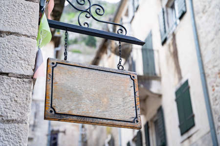 Clean wooden board hangs on wall of house on street, copy space for advertising or informational text. Sign of antique shop, old cafe or authentic shop.