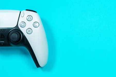Budva, Montenegro - March 16, 2021: New product from Sony, wireless white Play Station 5 gamepad on blue background.