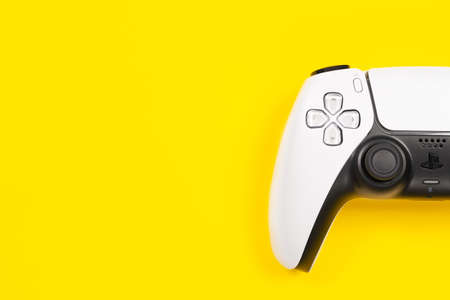 Budva, Montenegro - March 16, 2021: New product from Sony, wireless white Play Station 5 gamepad on yellow background.