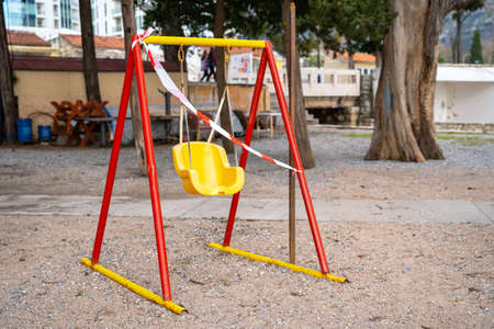 colored playground with swings in park is closed for repairs and fenced with red and white signal tape. Prohibition of visiting public places during state quarantine.