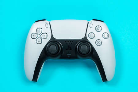 Budva, Montenegro - March 16, 2021: New product from Sony, wireless white Play Station 5 gamepad on blue background. top view