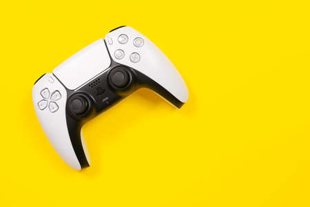 Budva, Montenegro - March 16, 2021: Wireless controller for video game console PlayStation 5 by Sony on yellow background, top view, copy space for advertising. Cool gift idea.