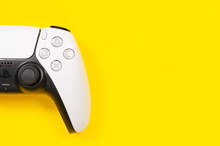 Budva, Montenegro - March 16, 2021: Half of white stylish wireless controller for video game console PlayStation 5 on left side of photo, yellow background, top view, copy space for advertising text.