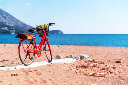 Red walking bike with basket full of necessary things for relaxing on beach, stands on boardwalk on sandy seashore. Outdoor activities during vacation or holiday.