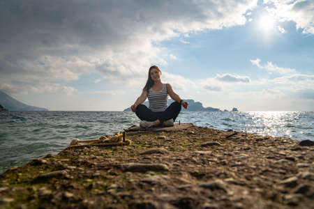 Young active brunette is sitting in lotus position on rocky seashore, front view from low angle, beautiful seascape on background. Woman on fitness and yoga tour for reboot.
