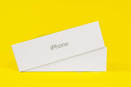 RUSSIA ROSTOV - MAY 29 2021: Half-closed box with new unpacked Apple iPhone lies on yellow background, side view, studio shot, copy space for advertising text.