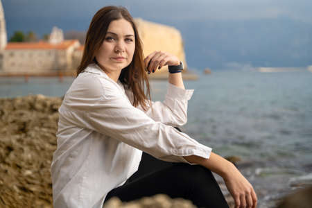 Young and attractive brunette woman on white shirt was tired of her former life and job, so she ran away from problems and went on vacation to reboot, change her lifestyle and rest.