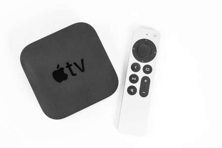 May 29, Rostov, Russia: New unpacked Apple TV console and Siri Remote control with a touch-enabled clickpad laying nearby on a white background, front view, copy space. Editorial