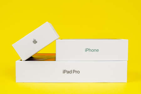 RUSSIA ROSTOV - MAY 29 2021: Three closed boxes for Apple digital devices stacked on top of each other on yellow background, side view, copy space for advertising text. A fan of the brand.