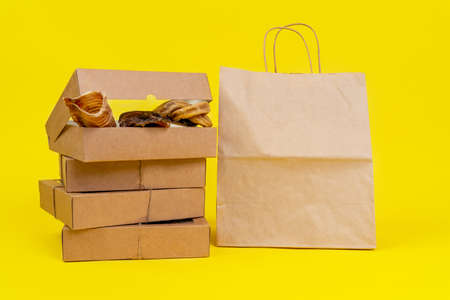 Dog treats made of dried meat in cardboard box with transparent cover, tied with twine, stands with an eco-friendly package on a yellow background, front view, copy space. Stock Photo
