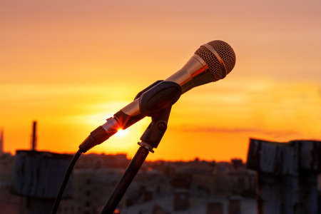 Microphone on the stand is prepared for recording song and video clip, or for outdoor musical show, close up. Roofs of houses and stunning golden sunset on the background, romantic view.