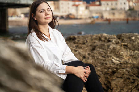 beautiful young brunette woman sits on stone pier and gazes thoughtfully out to sea, beautiful mountain range on background. Single woman travels alone. Restoration of mental health. Stock Photo