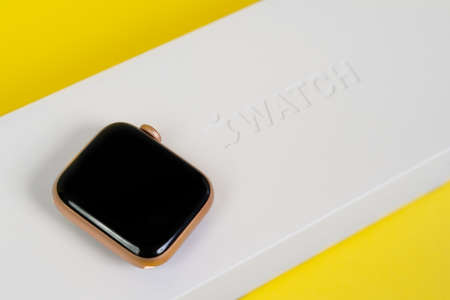 RUSSIA ROSTOV - MAY 29 2021: Apple Watch Series 6 on yellow background with display facing up, boxes are nearby, copy space. Smart device for active lifestyle. Editorial