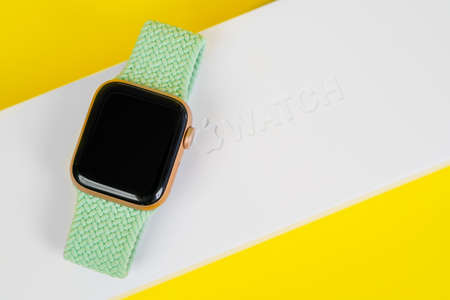 May 29, Rostov, Russia: Apple Watch Series 6 with green rubber strap on against of a white box yellow background, copy space. Smart device for an active lifestyle. Editorial