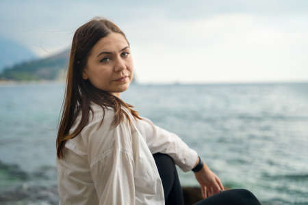 Young brunette in white shirt is sitting on rocky seacoast
