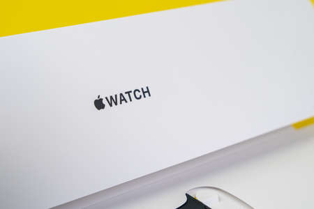 RUSSIA ROSTOV - MAY 29 2021:Half-opened box with new unpacked new generation of Apple Watch with band lies on yellow background, close up, studio shot.