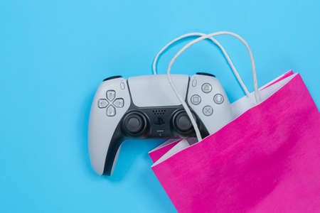 Budva, Montenegro - March 16, 2021: Recognizable design of DualSense wireless controller for PS5 with dynamic adaptive triggers and built-in microphone, lying on blue background with pink paper bag.