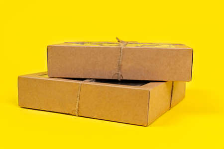 Cardboard recyclable boxes tied with a eco-friendly twine, for storage and delivery, on yellow background, copy space. Stock Photo