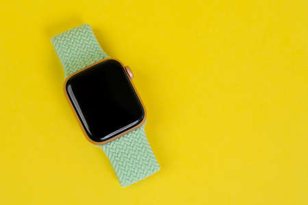 May 29, Rostov, Russia: Apple Watch Series 6 with green strap on yellow background, copy space. Smart device for an active lifestyle.