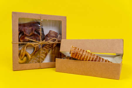 Kit of dried meat treats for training and encouraging dogs in recyclable eco-friendly cardboard boxes, yellow background, copy space. Stock Photo
