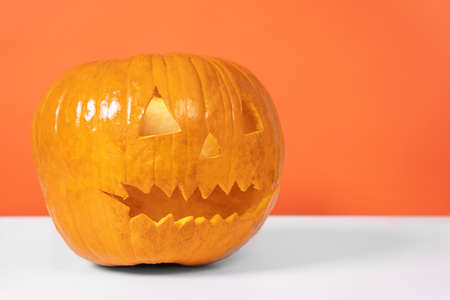 Plastic or ceramic candlestick or lamp in the form of jack-o-lantern made of orange pumpkin stands on the table, front view, copy space. Decoration for a Halloween party.
