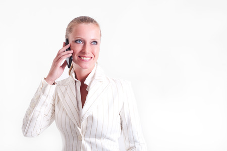 self confidence: Business woman answering a phone call with an open smile in her face  She radiates expertise and self confidence  She is wearing a white jacket with thin stripes and her hair is tied back   Stock Photo