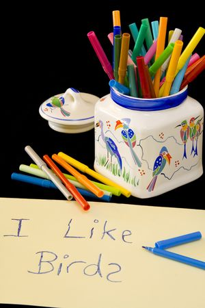 compostion: Childrens writing with blue crayons. Jar filled with color crayons in background. Compostion on black