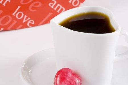 Freshly brewed coffee in white heart shape cup with words of love in background photo