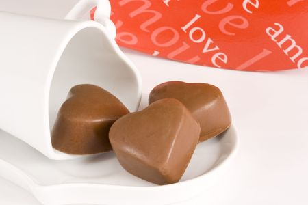 Three brown heart shaped chocolates placed on a heart shaped cup and causer with red box in background, all on white  photo