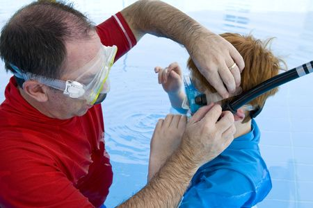 instruct: A father adjusting his sons snorkel and mask before swimming