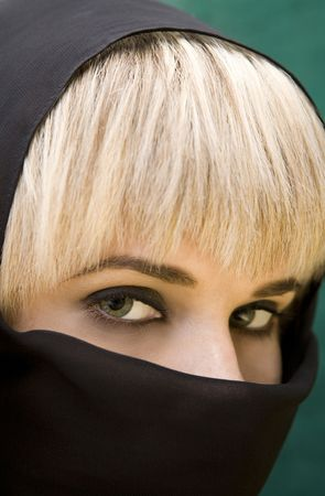 Closeup of beautiful Arabic woman with green eyes wearing a head cover photo